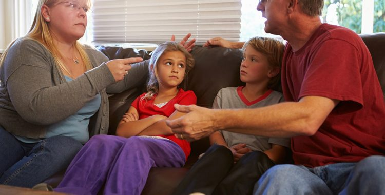 two kids sitting on sofa with parents arguing