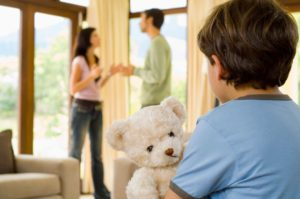 a child holds toy bear while parents argue in background