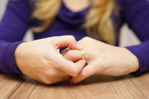 women clutches wedding ring - choosing divorce lawyer
