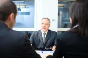 couple discuss mediation with professional in suit