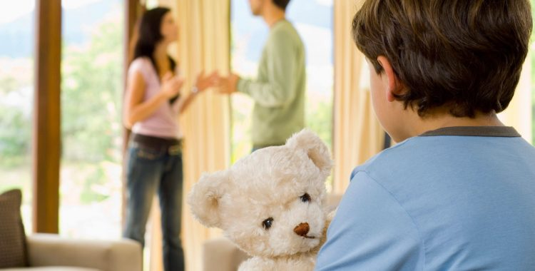 child in blue shirt holds toy bear while watching his parents fight causing alienation