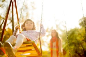 sole custody parent playing with her daughter on a swing