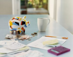 calculating attorney fees at a table with piggy bank and currency on table