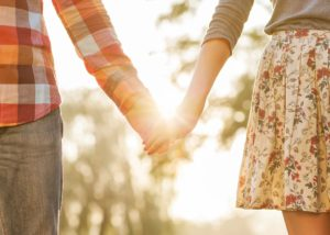a boomerang couple hold hands in sunlight