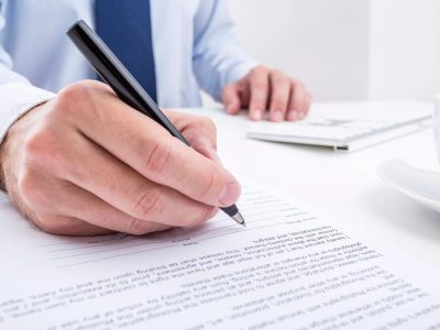 Man fills out form with pen while sitting at computer
