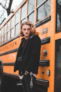 Blonde haired teenaged male waits for the bus