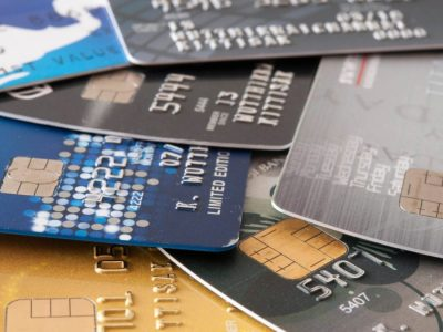 seven separate credit cards are laid out on table